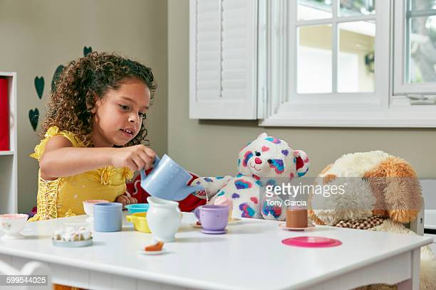 Girl in playroom sitting at table serving tea from toy tea set to soft toys