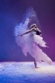 Woman in undrewear and pointe shoes jumping gracefully in a white dust cloud and color light profile view