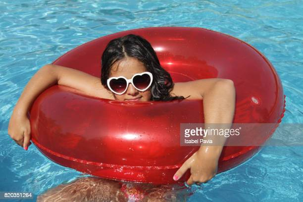 Girl in pool on red inflatable ring