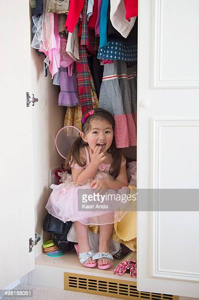 Girl in princess costume hiding in cupboard