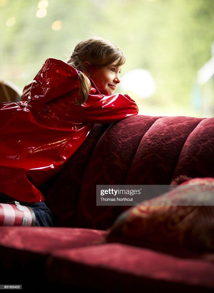 Girl in raincoat looking outside window : Stock Photo