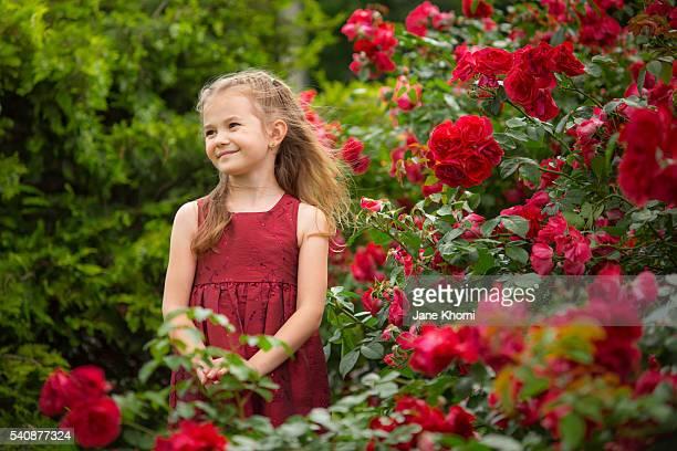 Girl in red dress in rose garden