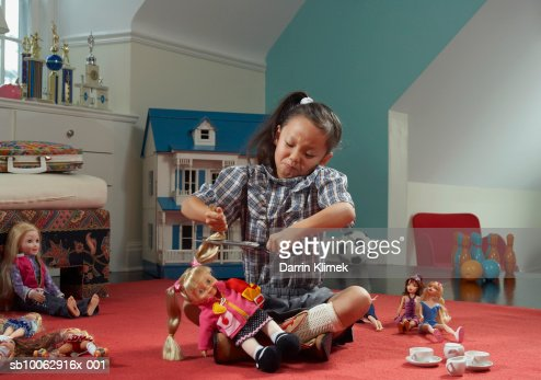 Girl (6-7 years) in room, cutting doll's hair : Stock Photo
