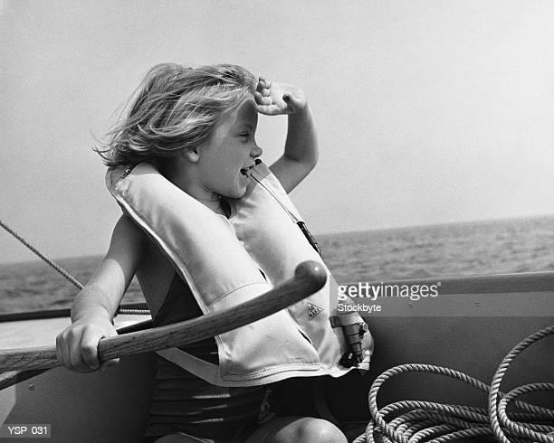 Ragazza in barca a vela, di indossare un giubbotto di salvataggio, con timone