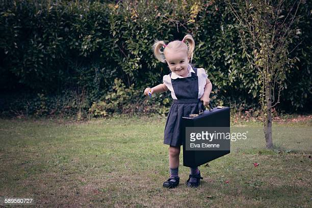 Girl (3-4) in school dress carying briefcase