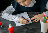 Girl in school uniform sits at a Desk and do homework