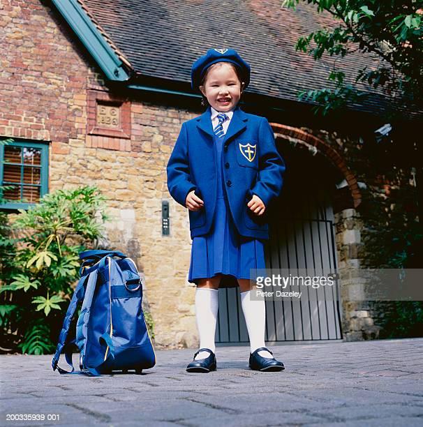 Girl (3-5) in school uniform, smiling, portrait, surface level