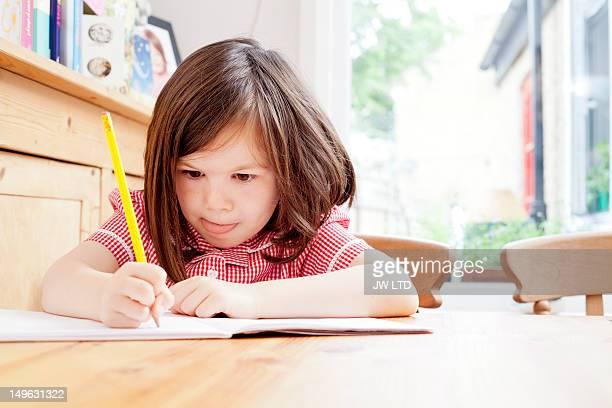 girl (4-5) in school uniform writing in book