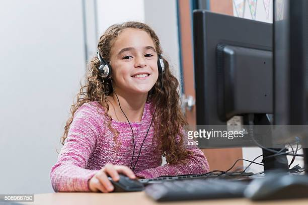 Girl in school using desktop computer wearing headphones