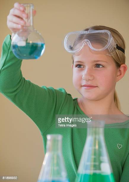 Girl in science class looking at beaker