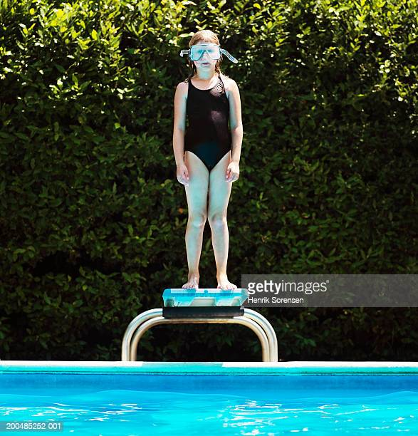 Girl (7-9) in scuba mask standing on springboard beside pool
