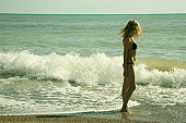 The girl and sea waves. An art photo. A beautiful landscape.