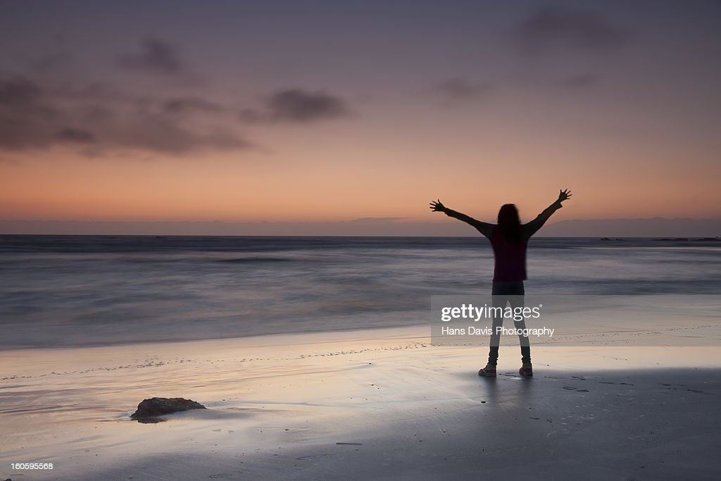 Girl in silhouette on beach with arms outstretched : Stock Photo