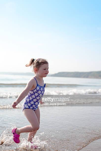 Girl in star swimsuit running on beach