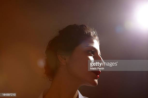Girl in studio with flare of light behind her