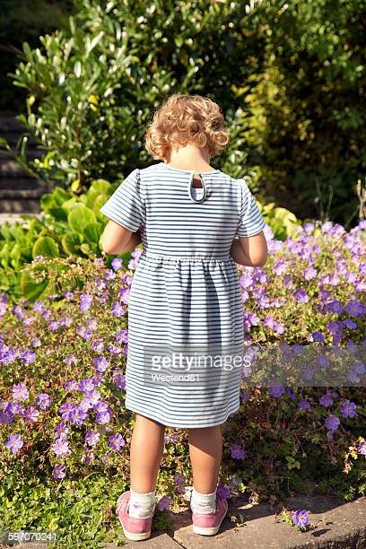 Girl in summer dress standing at flowers