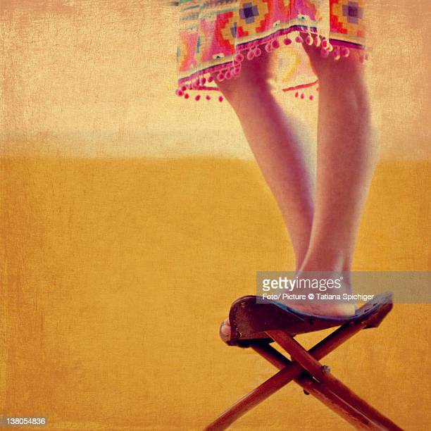 Girl in summer dress standing up on seat