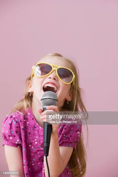 Girl in sunglasses singing into microphone