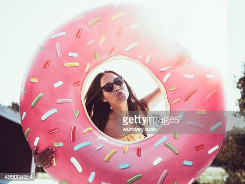 Girl in sunglasses with a pool inflatable blowing a kiss