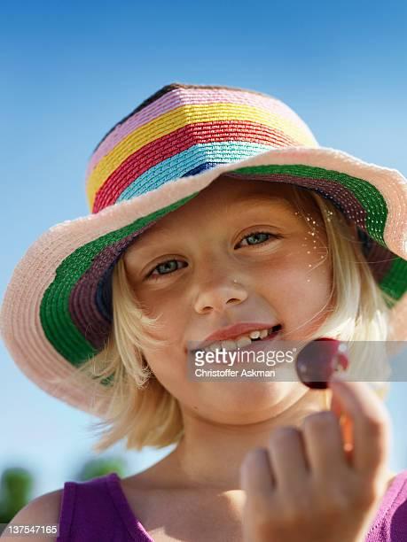 Girl in sunhat holding cherry