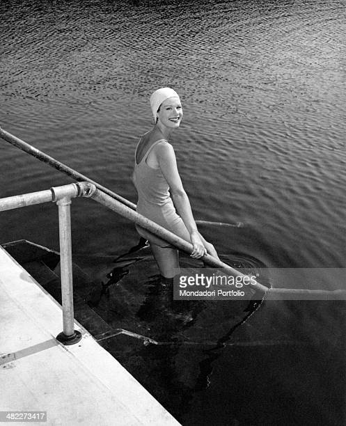 A girl in swim cap and swimsuit smiling on a pool ladder USA 1961