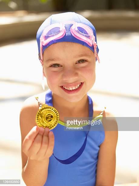 Girl in swimming costume holding medal (portrait)