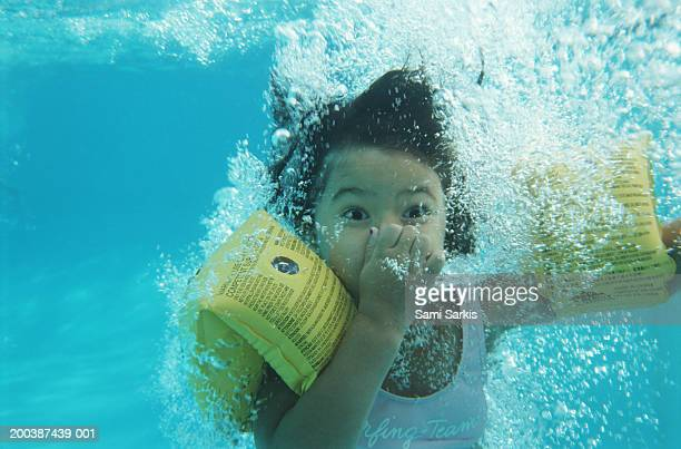 Girl (8-10) in swimming pool, holding nose underwater, close-up