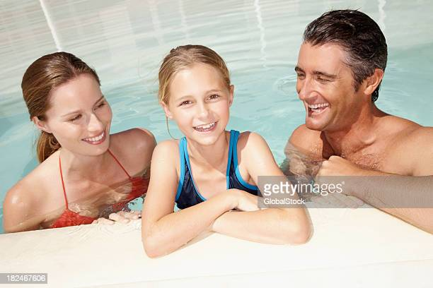 Girl in swimming pool with her parents on vacation