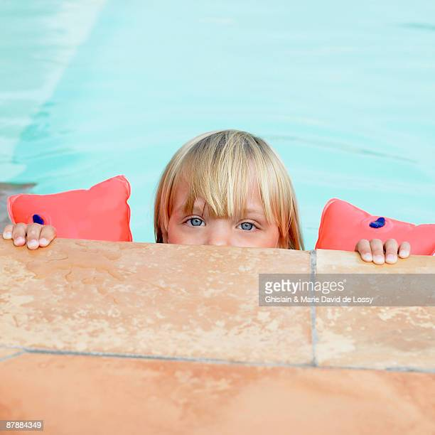 Girl in swimming pool with rubber rings