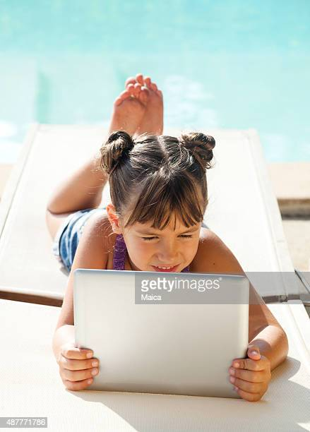Girl in swimming pool with tablet