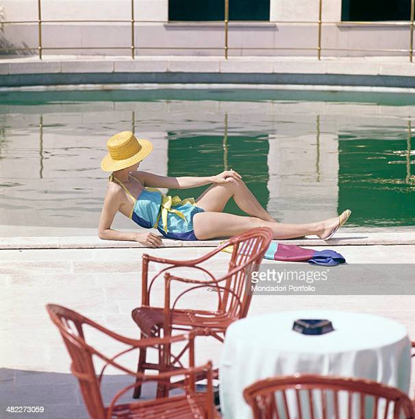 A girl in swimsuit and straw hat sunbathing by the swimming pool 1960s