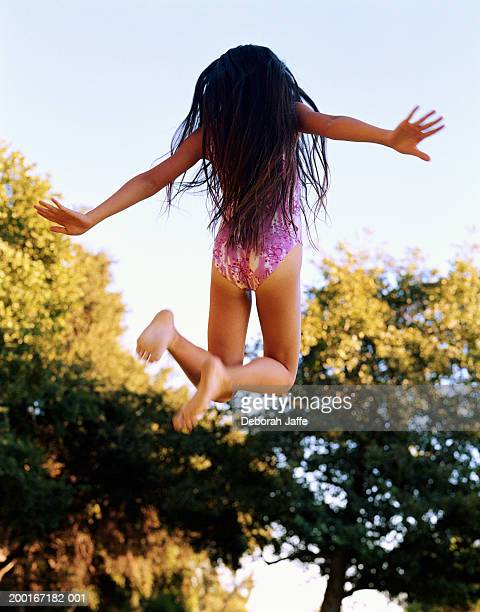 Girl (9-11) in swimsuit jumping, rear view