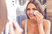 Beautiful young woman is cleaning her face using a cotton disc and smiling while looking in the mirror in the bathroom