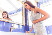 Low angle view of beautiful young woman in gray undershirt feeling pain, standing in the bathroom