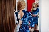Sales consultant helps to dress the dress for buyer at boutique.