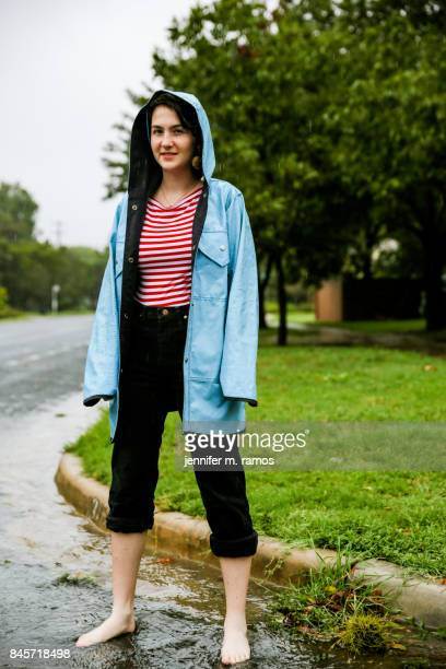 Girl in the Rain wearing a blue raincoat standing in the street Austin Texas