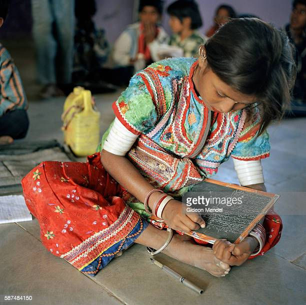 A girl in traditional Meghwal attire concerntrates on their schoolwork at the local school in Harijan Vas which has a total of 75 pupils ranging in...