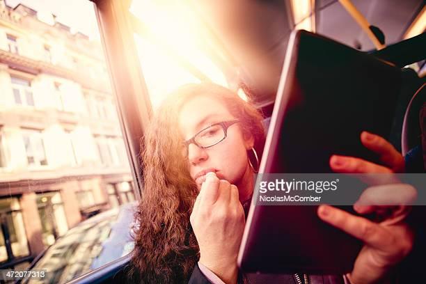 Girl in transit applying make-up using tablet