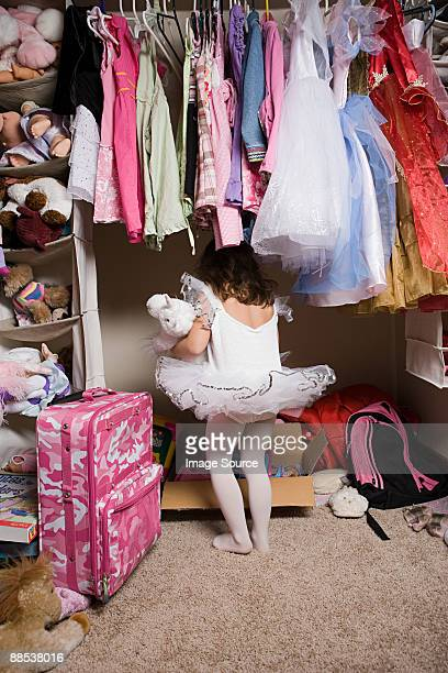 Girl in tutu looking in closet