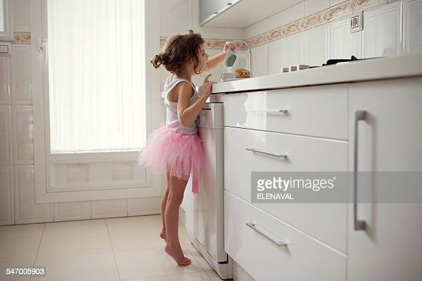 Girl in tutu standing in kitchen pouring milk into a cup