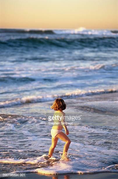Girl (3-5) in underwear, running in surf on beach, rear view