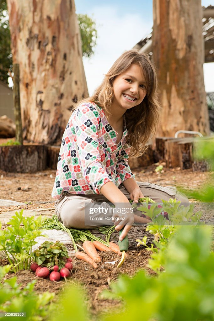 Girl (8-9) in vegetable garden : Stock Photo
