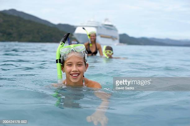 Girl (10-12) in water with snorkel gear smiling, portrait