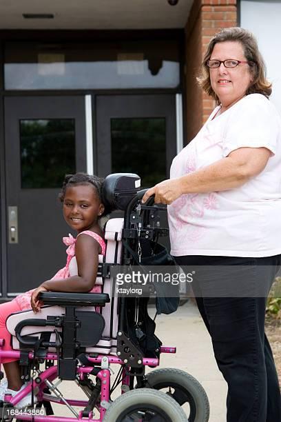 Ragazza in sedia a rotelle spinte a scuola con insegnante