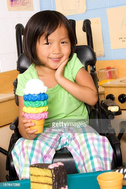 Girl in wheelchair holding toy ice cream cone