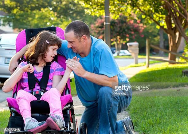 Ragazza in sedia a rotelle tiene Daddy's mano