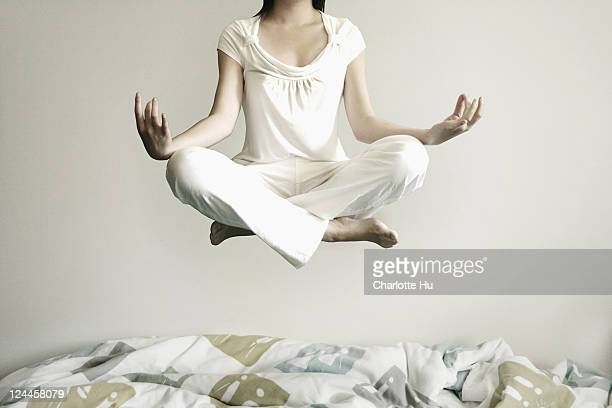 Girl in white, meditating and levitating