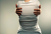 cross processed image of girl in short sleeved white t shirt from back holding herself