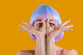 Model in colorful short wig showing eyes through fingers with feeling of astonishment.