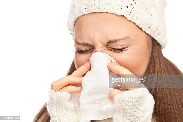 Girl in winter clothing sneezing